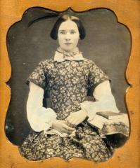Woman seated with book, circa 1855